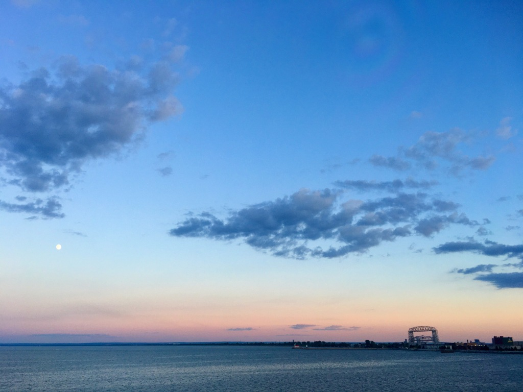 Moon rising over Lake Superior, with lift bridge silhouette.