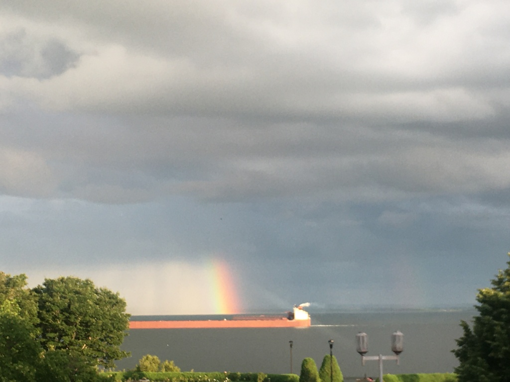 Tanker ship on Lake Superior with a rainbow in the background.