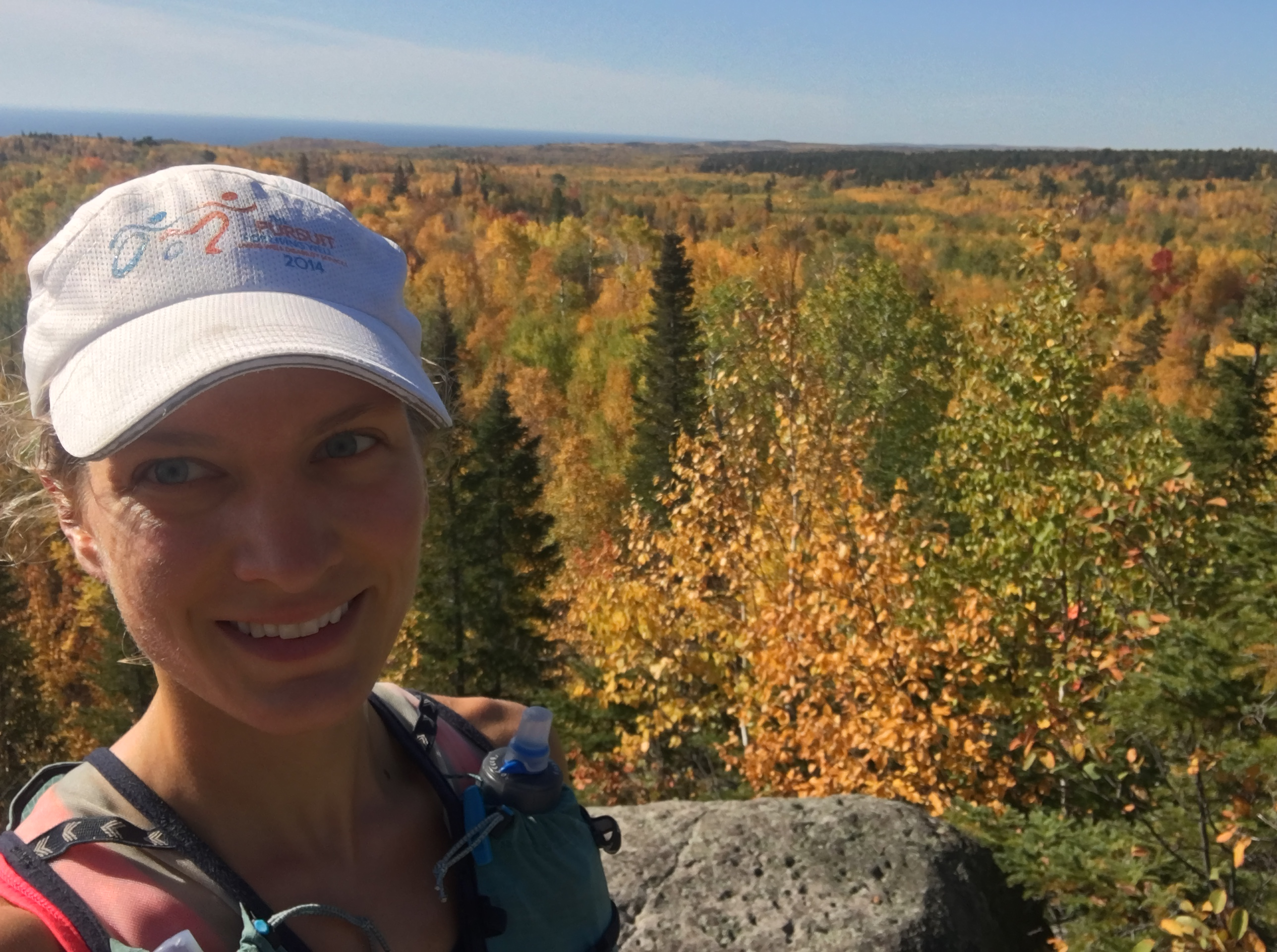 A trailrunner on a ridge with fall colors in the background