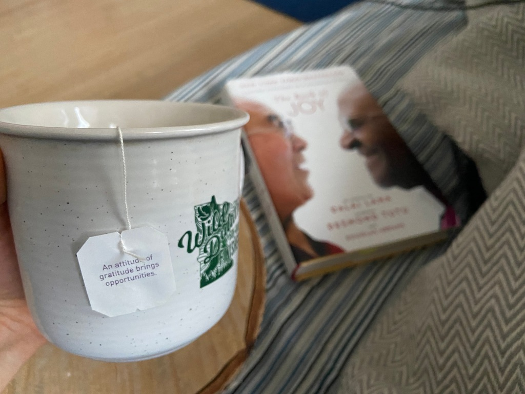 A hand holding a mug of tea, with The Book of Joy in the background